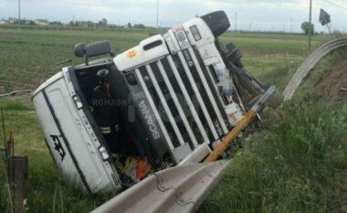 Kamioni del nga rruga e përmbyset, shoferi ende brenda mjetit